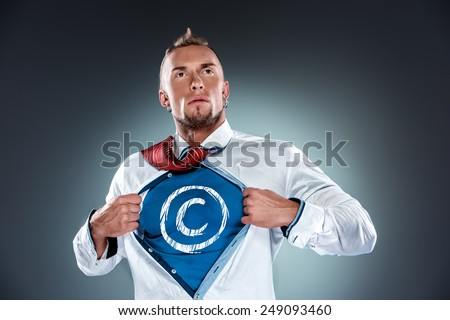 businessman acting like a superman and tearing his shirt off on a gray background. concept of uniqueness and diversity - stock photo
