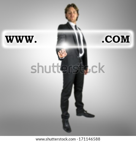 Businessman activating a web address with words www and dot com with copyspace between in a navigation bar on a virtual interface or screen with his finger from behind - stock photo