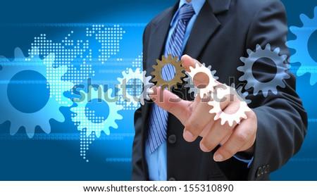 businessman adding a cog gear - stock photo