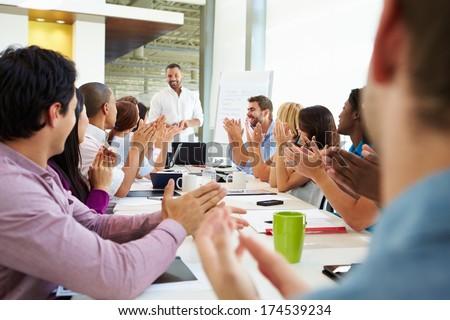 Businessman Addressing Meeting Around Boardroom Table - stock photo