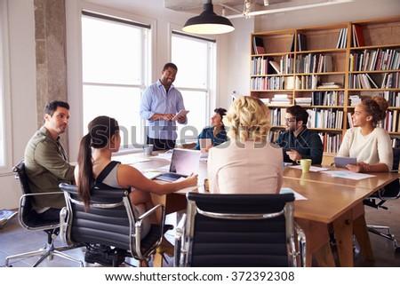 Businessman Addressing Team Meeting Around Table - stock photo