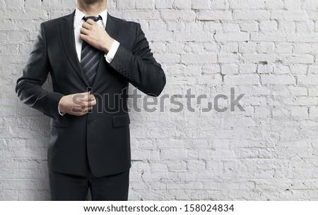 businessman adjusts his tie on brick wall background - stock photo