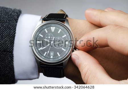 businessman adjusts the time on his wristwatch - stock photo