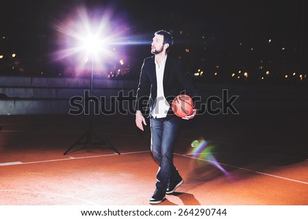 Businessman after hard working day plays basketball - stock photo
