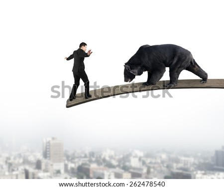 Businessman against black bear balancing on wooden board with urban scene background - stock photo