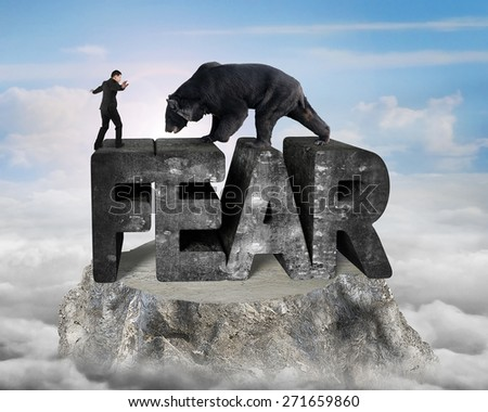 Businessman against black bear standing on fear 3D mottled concrete word, on top of mountain peak with sunny sky clouds background - stock photo