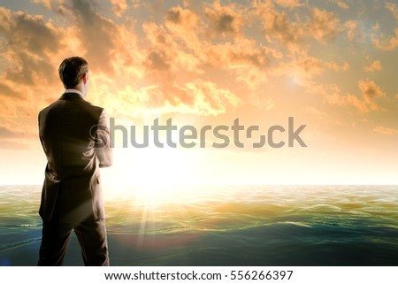 Businessman against sea in morning light, rear view