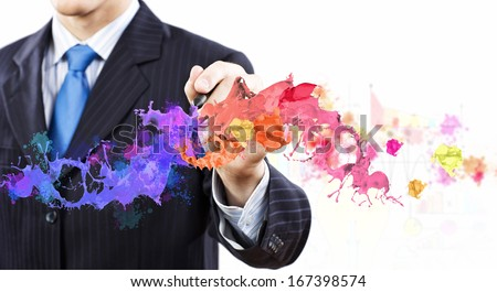 Businessman against white background drawing colorful splashes with marker - stock photo