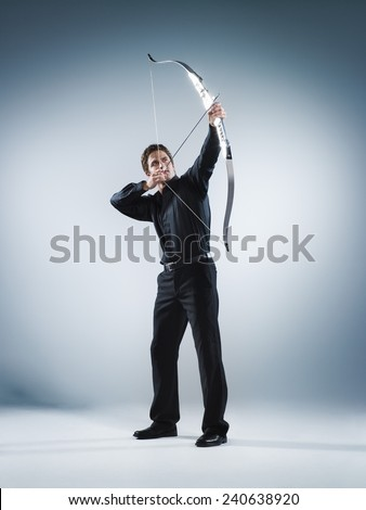 Businessman Aiming a Bow - stock photo