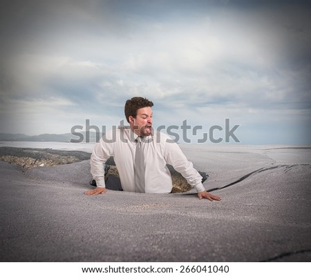Businessman alone and afraid swallowed by asphalt - stock photo