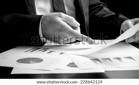 Businessman analysing a set of bar, pie and triangular graphs as he sits at his desk pointing to one document he is holding, close up greyscale in a business analysis, projections and strategy concept - stock photo