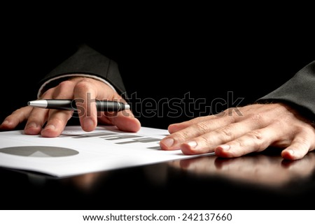 Businessman analyzing a set of graphs, isolated over black background. - stock photo