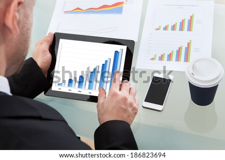Businessman analyzing an increasing bar graph on a tablet computer with paper printed graphs laid out on his desk with a mobile and mug of coffee  over the shoulder view of the screen - stock photo