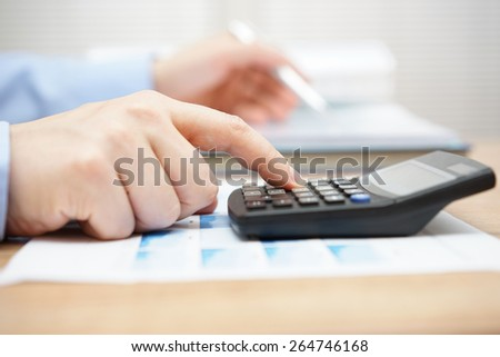 Businessman analyzing business data and using calculator - stock photo