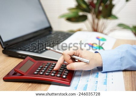 businessman analyzing business data with calculator,laptop,reports - stock photo