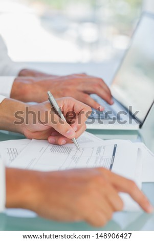 Businessman analyzing documents while other working on laptop