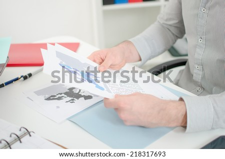 Businessman analyzing economic documents at the office