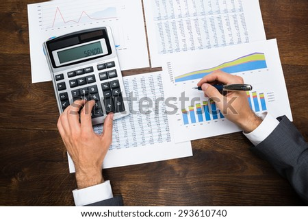 Businessman Analyzing Graph And Doing Financial Calculations - stock photo