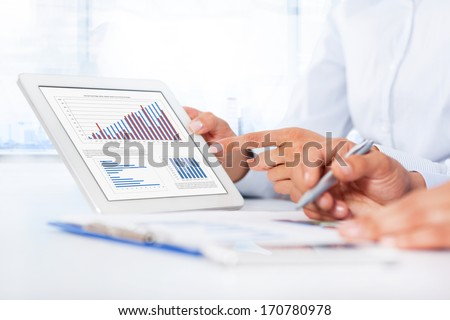 Businessman analyzing graph using digital tablet touch pad, touching hand point finger touch screen, business people group desk office, businesspeople report financial charts - stock photo