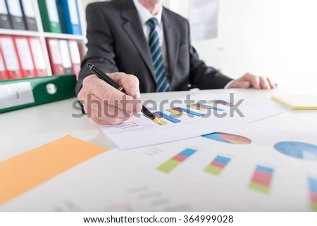 Businessman analyzing graphs at office - stock photo