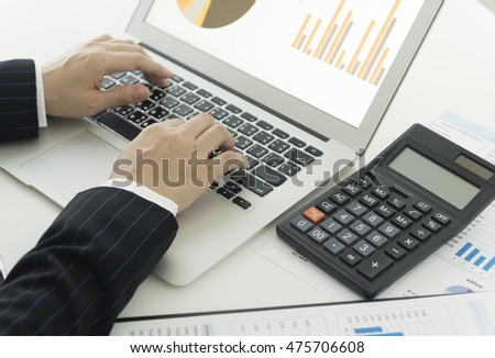 Businessman analyzing investment charts and business graphs with laptop computer. Accounting concept. top view. .