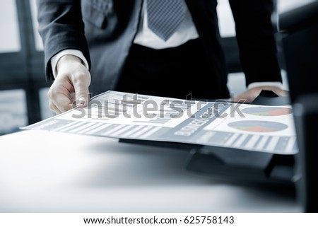 Businessman analyzing investment charts with printer. Accounting