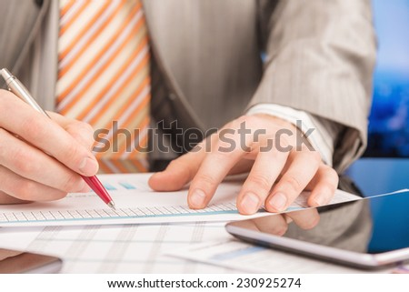 Businessman analyzing report - stock photo