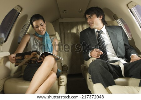 Businessman and a businesswoman sitting in a private airplane - stock photo