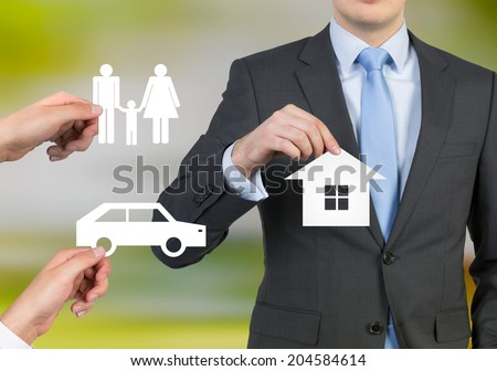 Businessman and a concept of a dream life: a family, a car and a house. - stock photo