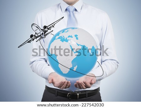 Businessman and an airplane circling the globe  - stock photo