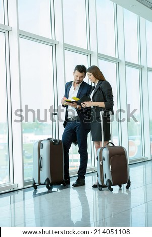 Businessman and business woman communicating to the flight at airport