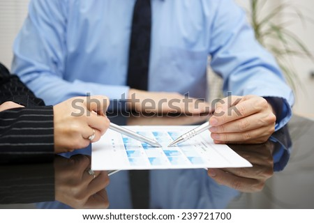 businessman and businesswoman are analyzing report with full of graphs - stock photo
