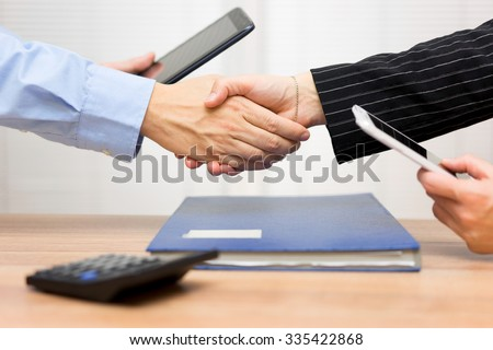 businessman and businesswoman are handshaking  after video call  or presentation with tablet computer and mobile phone
