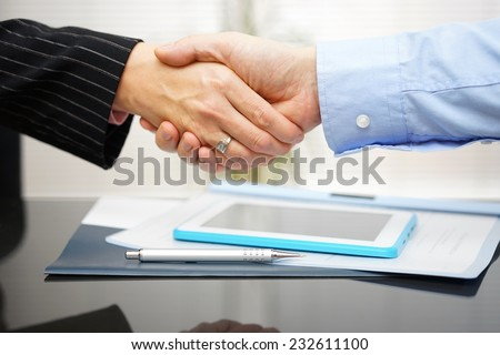 businessman and businesswoman are handshaking over documents and presentation - stock photo