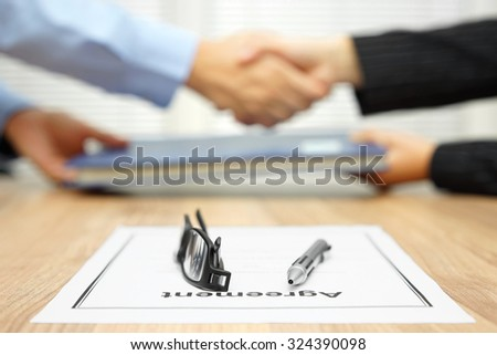 businessman and businesswoman are shaking hands and exchanging folder  after agreement was reached - stock photo