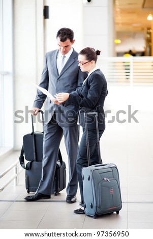 businessman and businesswoman at airport - stock photo