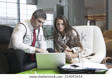 Businessman and businesswoman at meeting with laptop - stock photo