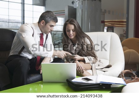 Businessman and businesswoman at meeting with laptop and tablet - stock photo