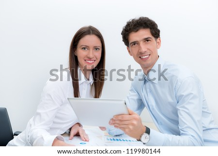 Businessman and businesswoman at the workplace planning with digital tablet. - stock photo