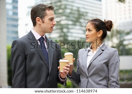 Businessman And Businesswoman Chatting In Street Holding Takeaway Coffee - stock photo