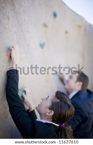 Businessman and businesswoman climb the same wall - stock photo
