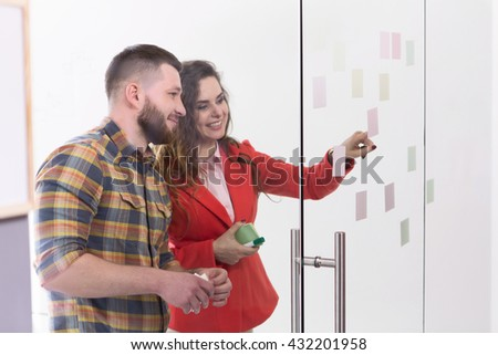 Businessman and businesswoman communicating about business things while working in office. People reading sticks on glass doors. - stock photo