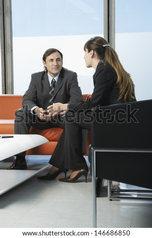 Businessman and businesswoman communicating while sitting in office lobby - stock photo