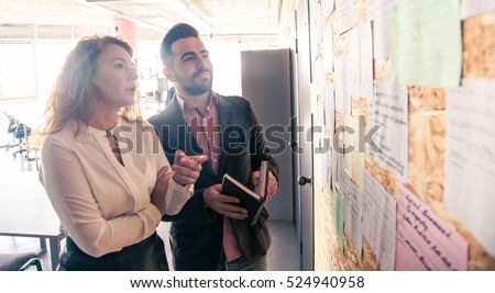 Businessman and businesswoman communicating while standing near board in office. People discussing following meetings in board room soon.