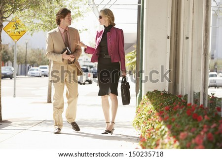 Businessman and businesswoman communicating while walking on sidewalk - stock photo