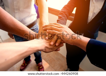 Businessman and Businesswoman,Concept of teamwork: Close-Up of hands business team showing unity with putting their hands together. - stock photo