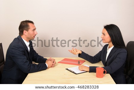 Businessman and businesswoman discussing plans at meeting