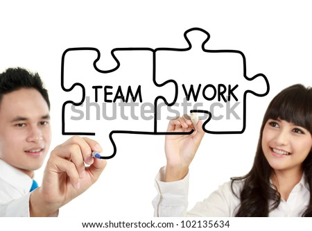 "businessman and businesswoman drawing ""teamwork"" written in puzzle - stock photo"