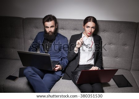 businessman and businesswoman dressed in suit and with laptop, phone and tablet; woman and man working with portable computers and devices; guy and girl with notebooks, smartphones and tabs;