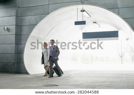Businessman and businesswoman entering railroad station - stock photo